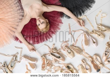 Tender ballerina lies on the colorful tutus on the white floor in the studio. She wears a light top. Below her there are many pointe shoes. Tutus are peach, burgundy and black. Closeup. Horizontal.