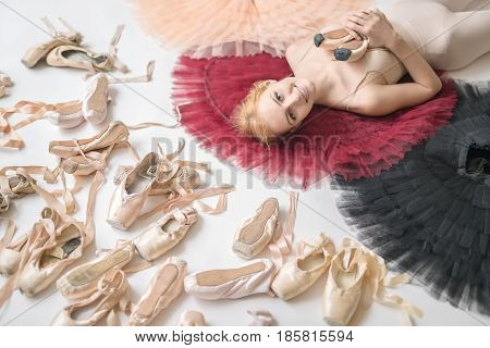 Smiling ballerina lies on the colorful tutus on the white floor in the studio. She wears a light top and holds pointe shoes. On the left there are many ballet shoes. Closeup. Horizontal.