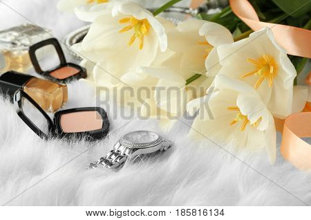 Beautiful composition of cosmetics with tulips on furry background