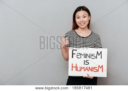 Image of young happy woman standing over grey wall showing thumbs up. Looking at camera holding blank with text about feminism.