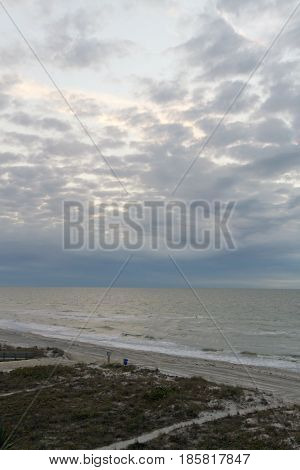Indian Rocks Florida USA - January 27 2017: Atmospheric early morning view of Indian Rocks Beach and the Gulf of Mexico in winter lit by a breaking cloud cover on January 27 2017 in Indian Rocks Florida