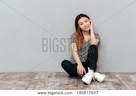 Photo of young happy lady sitting on floor over grey wall. Looking at camera.