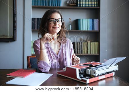 Portrait of a mature smiling authoress sitting at the desk with typewriter and looking at camera