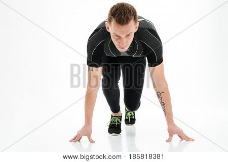 Portrait of a focused young male sprinter preparing to start running isolated over white background