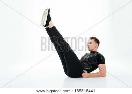 Full length portrait of a serious healthy sportsman doing abdominal exercises on the floor isolated over white background