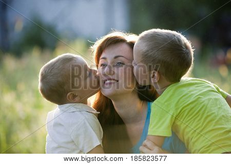 Happy mother with two children in garden. Happy young boys kisses mother.