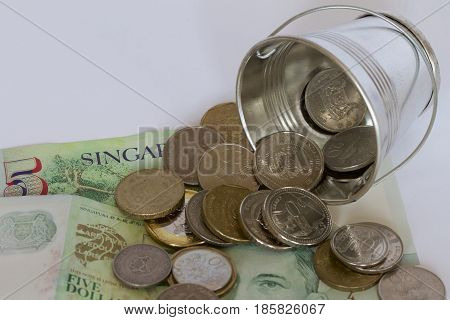Singaporean dollars and cents and a silver bucket.