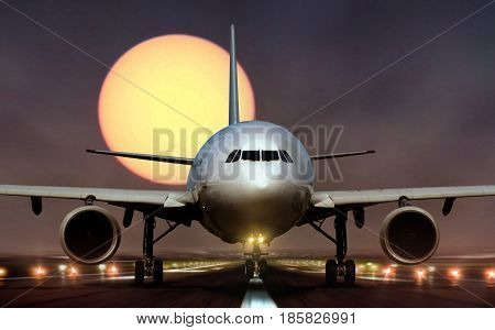 Commercial airplane landing on runway during sunset