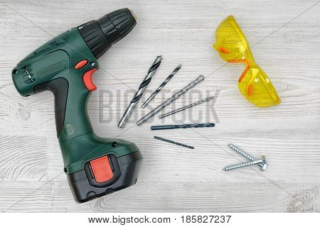 A cordless drill set on a wooden table background with a set of bits in the box and yellow protective glasses around. Manual labor. Home improvement. Handyman tools.