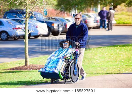 Disabled ten year old boy in wheelchair walking at park with father or caregiver