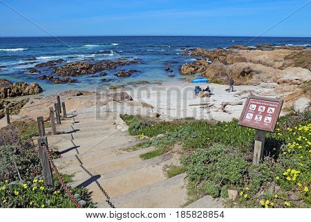 PACIFIC GROVE CALIFORNIA - MARCH 17 2017: Stairway entrance sign and people enjoying the surf rocks and sand of the park at Asilomar State Beach on the Monterey Peninsula.