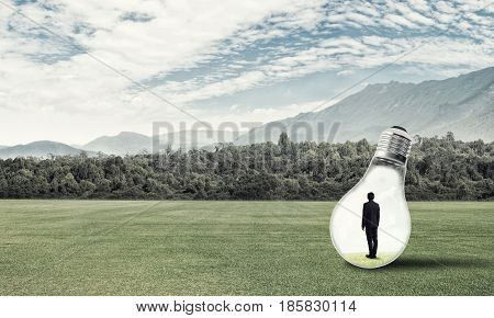 Young businessman trapped inside of light bulb on countryside road