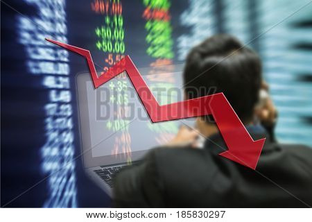 Motion blur of down trend arrow line chart with trader and computer in the marketing room on blurred stock board background in business concept