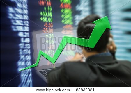 Motion blur of up trend arrow line chart with trader and computer in the marketing room on blurred stock board background in business concept
