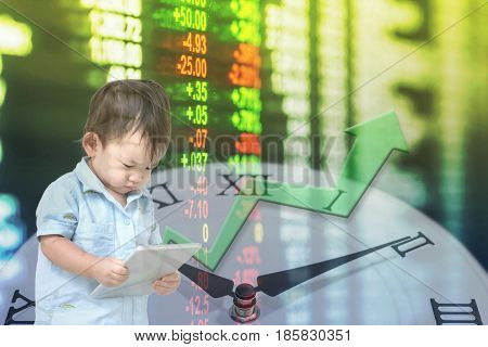 Motion blur of asian kid start to learn about invest with tablet in his hand on blurred stock board and clock background in investment concept