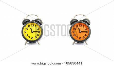 Closeup yellow alarm clock and orange alarm clock for decorate show a quarter past eleven o'clock or 11:15 a.m. isolated on white background