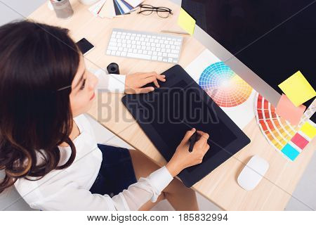 High Angle View Of A Photo Editor Working At Desk In Creative Office