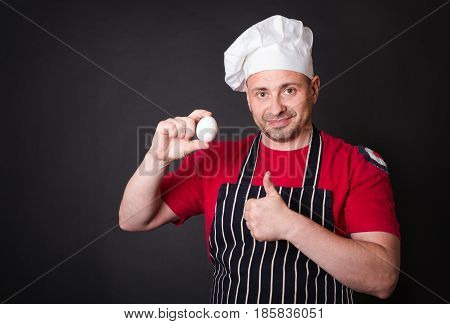 Chef with chicken egg in studio on a black background.