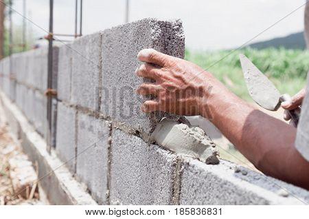 bricklayer installing bricks Masonry work in construction site