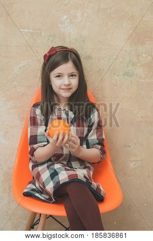Little Girl With Orange In Hand Sitting In Plastic Chair