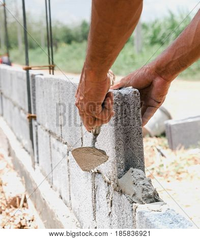 bricklayer installing bricks Masonry work in construction site