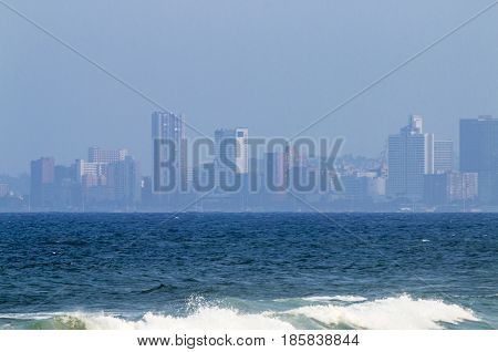 Waves And Ocean Against Smoggy Ccty Skyline