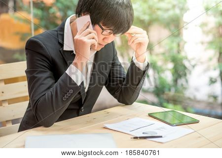 frustrated stressed business man checking chart and diagram report paper in workplace young Asian entrepreneur contact customer and worried about job process risk management concepts