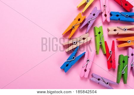 Colored clothespins on a pink background. Empty space for copy paste text