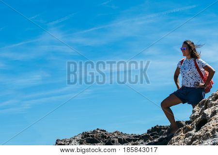 Woman with backpack standing on rock and admiring view.