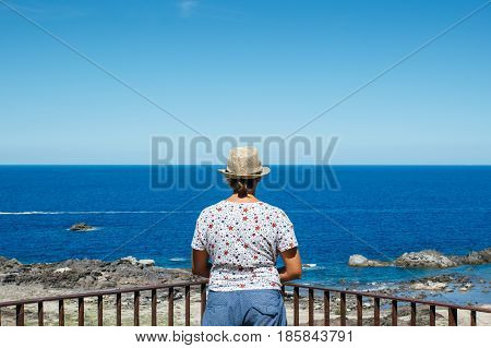 An unrecognizable woman standing at the fence and admiring the seascape.