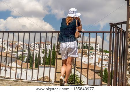 view of young women looking at city of ronda from a balcony spain