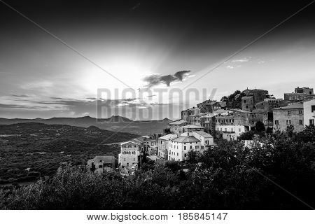 Black & White image of ancient hilltop village of Belgodere in the Balagne region of Corsica lit up by a dramatic evening sunset
