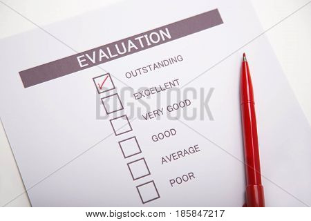 Evaluation checklist and red pen on white desk