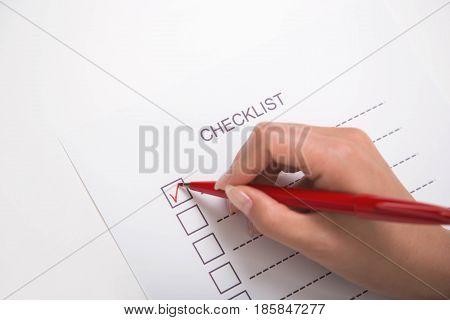 Close-up of hand marking on checklist with red pen