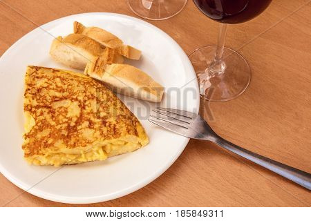 A photo of a tortilla, traditional Spanish potato omelette, with a fork, white bread, glasses of red wine, and a place for text. Typical tapas