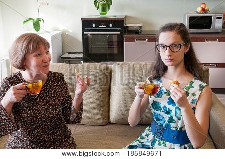 Grandmother and granddaughter drink tea and cookies in the kitchen