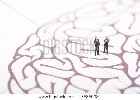 Businessman trapped in brain maze on white background