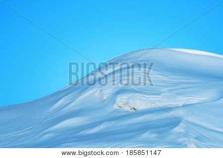 Abstract snow background snowcapped mountain hill on sunny winter day