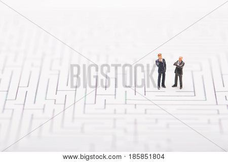 Businessman trapped in maze on white background