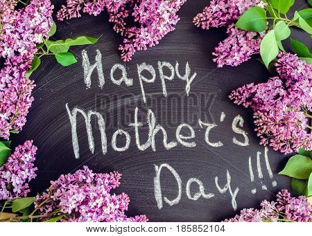 Wording Happy Mother's Day on chalkboard background with lilac flowers.