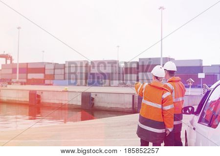 Workers in protective clothing examining cargo in shipping yard