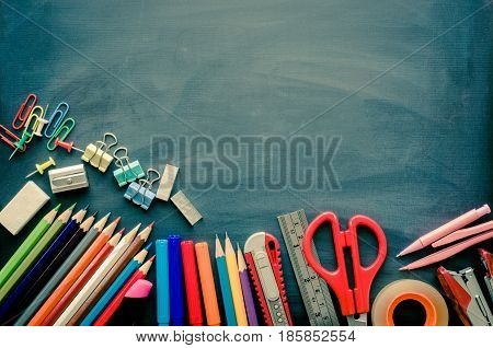 School supplies placed on a background blackboard concept ready for school.