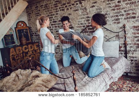 Attractive girls have fun and fight pillows on the bed.