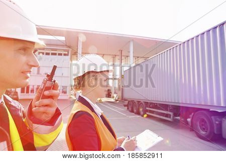 Male and female workers working in shipping yard