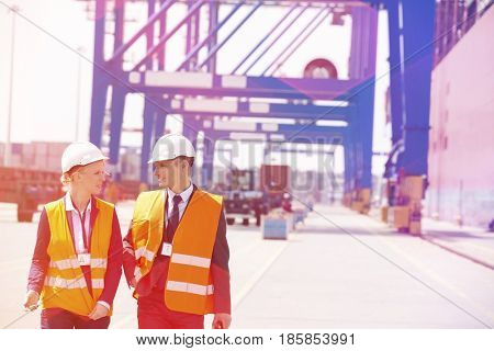 Engineers conversing while walking in shipping yard