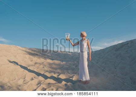 Young tender beautiful blonde woman in the desert with goldfish in her hands