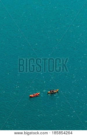 Unrecognizable people enjoying hot summer afternoon in boats on lake Bled aerial view of leisure and recreational activity for holiday vacation in Slovenia