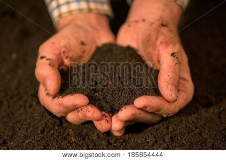 Handful of arable soil in hands of responsible male farmer close up selective focus