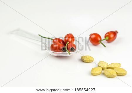 Rose hip on a medicine spoon on white background with yellow vitamine pills symbolising that drinking and eating of rose hip products prevents diseases like flu, sore throat, high temperature, vitamine pills are made also from rose hip, vitamine C