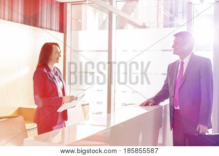 Businessman talking with receptionist in office